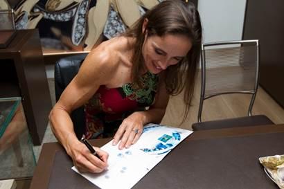 Fabiana Beltrame autografando o catálogo especial (Foto: Divulgação)